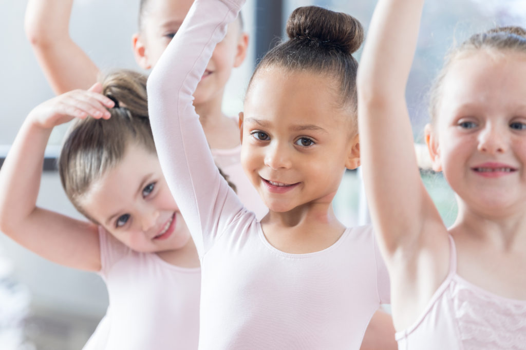 Beautiful mixed race little girl practices ballet with her friends.